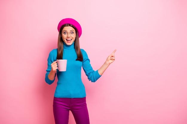 Portret van verbaasd gek meisje houdt mok espresso volg ongelooflijke zwarte vrijdag kortingspunt wijsvinger kopie ruimte draag blauwe paarse broek broek hoofddeksels. Premium Foto