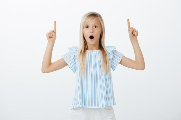 Portret van verbaasd verbaasd schattig jong meisje met blond haar, kaak laten vallen van verwondering en naar boven gericht, prachtig nieuws delen met zus, opgewonden en opgewonden over grijze muur Gratis Foto