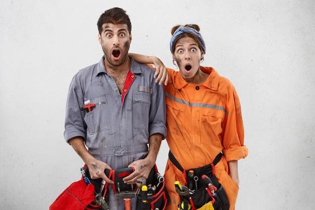 Portret van verbaasde geschokte elektriciens beseft dat ze tijdens het werk een fout hebben gemaakt Gratis Foto