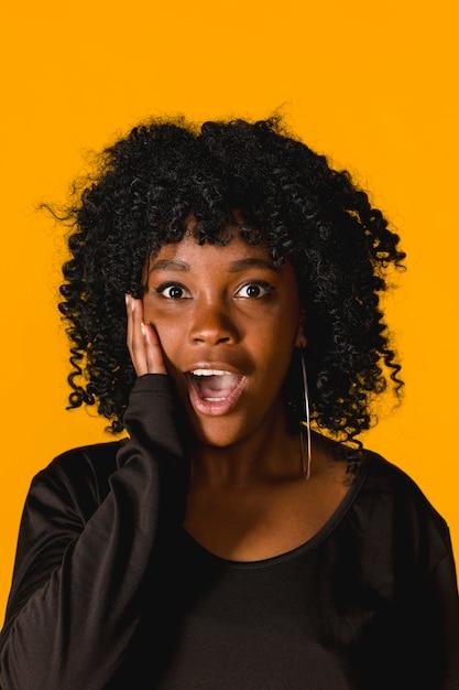 Portret van verbaasde jonge afrovrouw op gekleurde achtergrond Gratis Foto