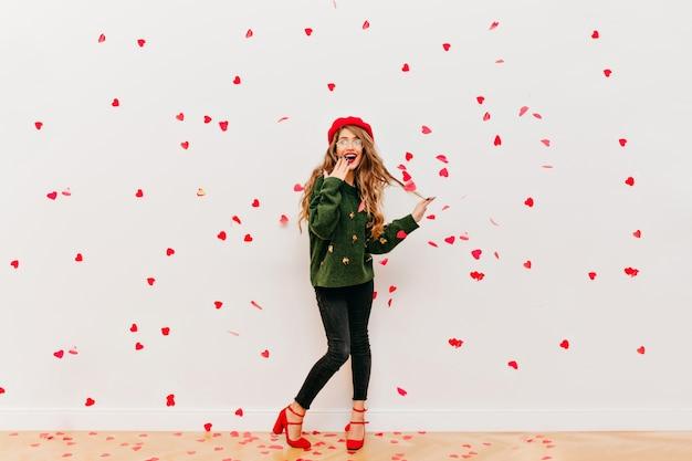 Portret van verbaasde langharige vrouw in rode baret met plezier in studio Gratis Foto