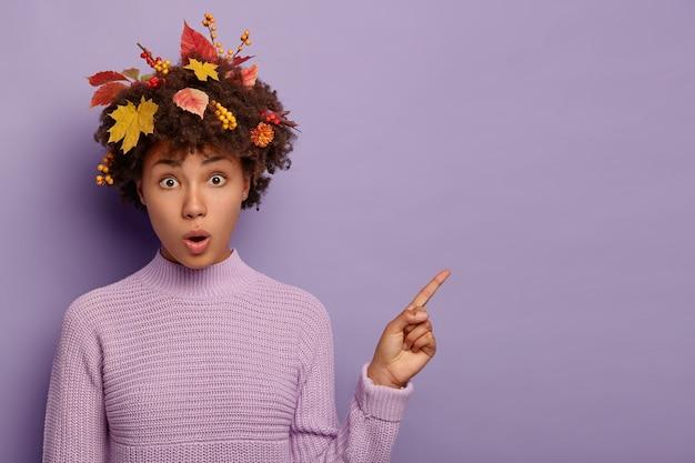 Portret van verbaasde vrouw met donkere huid wijst op kopie ruimte, opent mond, heeft herfstbladeren en lijsterbessen in het haar, staat sprakeloos en onder de indruk, draagt een gebreide paarse trui. Gratis Foto