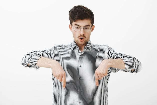 Portret van verbijsterde sprakeloze jongeman in stijlvolle bril en gestreept overhemd, kijkend en wijzend naar beneden terwijl hij zijn kaak laat vallen, iets ongelooflijks ziet, zich verbaasd voelt terwijl hij over een grijze muur staat Gratis Foto