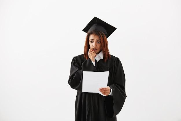 Portret van verdrietig verward onzeker afrikaanse vrouwelijke universitair afgestudeerde voorbereiding op haar acceptatie toespraak of test houden. Gratis Foto