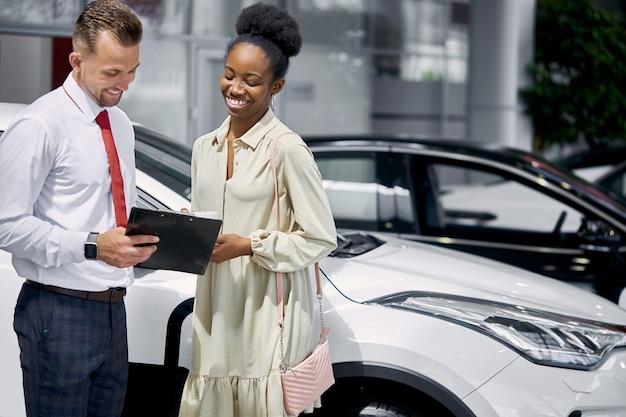 Portret van verkoper en afrikaanse vrouwencliënt die gesprek in autotoonzaal hebben Premium Foto