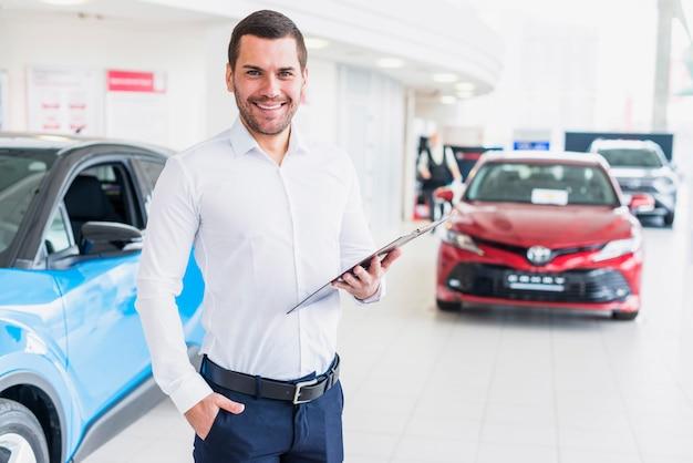 Portret van verkoper in het autohandel drijven Gratis Foto
