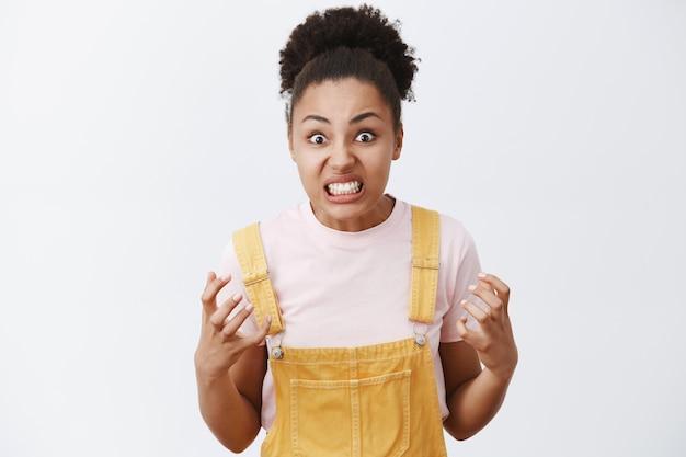 Portret van verontwaardigde pissige en boze schattige donkere vrouw met afro kapsel, gebalde vuisten en staren met haat Gratis Foto