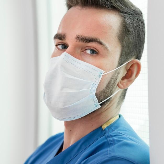Portret van verpleegster die preventiemasker draagt Gratis Foto