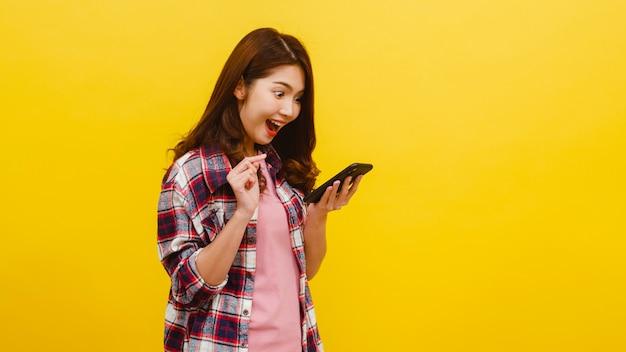 Portret van verrast aziatische vrouw met behulp van mobiele telefoon met positieve expressie, gekleed in casual kleding en camera kijken op gele muur. de gelukkige aanbiddelijke blije vrouw verheugt zich succes. Gratis Foto