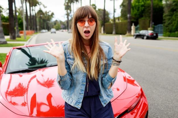 Portret van verrast brunette vrouw zittend op de motorkap van geweldige rode cabriolet sport auto in californië close-up. Gratis Foto
