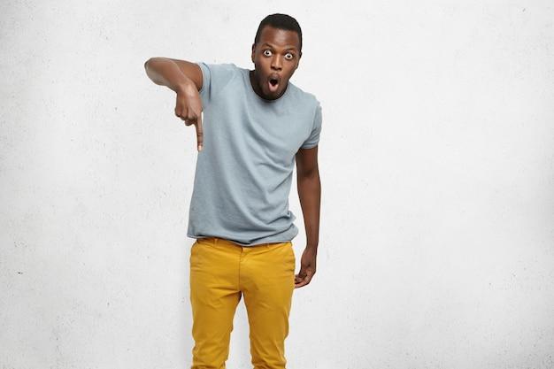 Portret van verrast en geschokt stijlvolle jonge zwarte klant met een verbaasde blik wijzende wijsvinger naar beneden, met daling van de prijzen. Gratis Foto