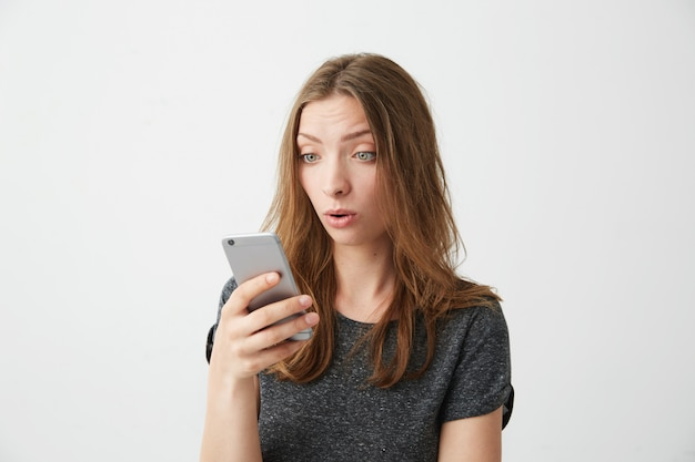Portret van verrast jong mooi meisje dat het telefoonscherm bekijkt met geopende mond die wed internet surft. Gratis Foto