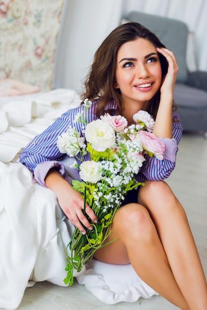 Portret van verse vrij vrolijke brunette vrouw in gestreepte t-shirt zittend op de vloer met lentebloemen in handen Gratis Foto