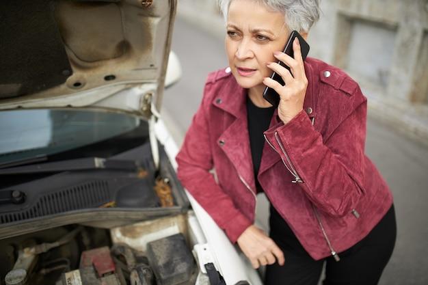 Portret van verstoorde europese vrouw van middelbare leeftijd met grijs kort haar die zich bij haar kapotte auto met open kap bevinden omdat motorstoring Gratis Foto