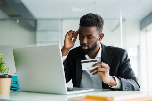 Portret van vertrouwen jonge afrikaanse man met creditcard met laptop betalen via internet Gratis Foto