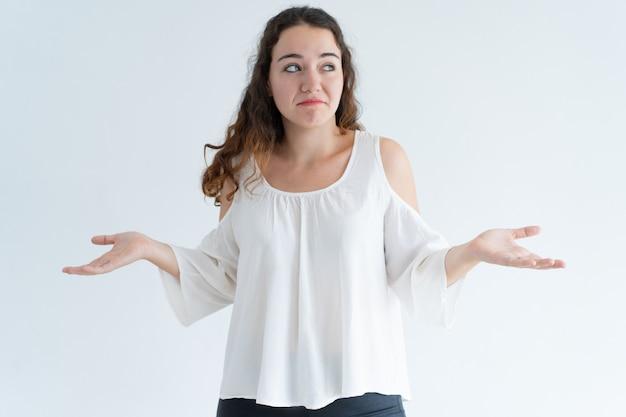 Portret van verwarde jonge vrouw die schouders ophalen Gratis Foto