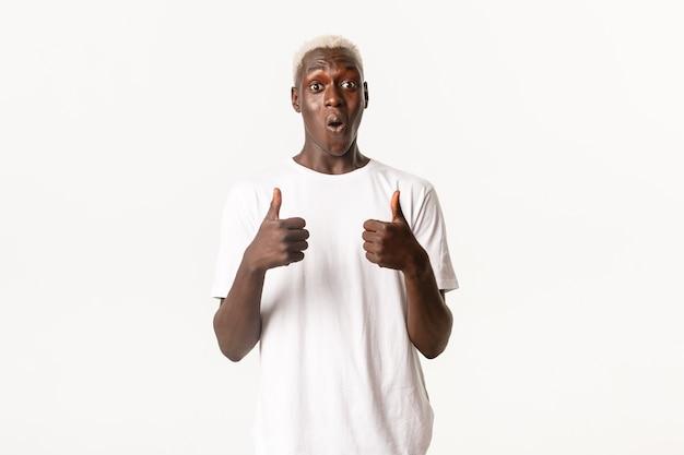 Portret van verwonderde en onder de indruk afro-amerikaanse blonde man, gefascineerd duimen omhoog Premium Foto