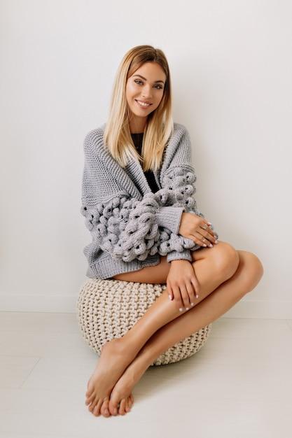 Portret van volledige lengte van mooie gelukkige vrouw met blond haar en lange mooie benen die pullover dragen die over geïsoleerde muur zitten Gratis Foto
