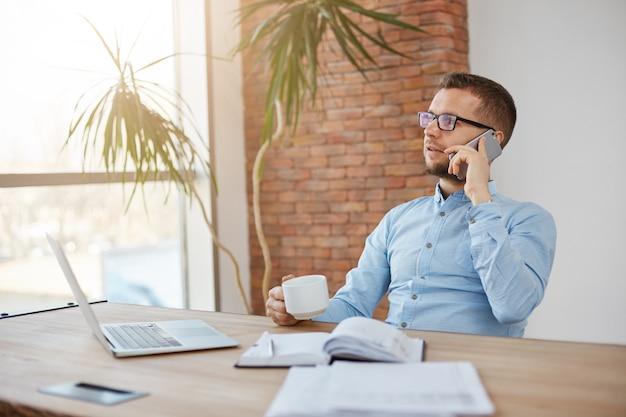 Portret van volwassen bebaarde drukke mannelijke bedrijfsdirecteur in glazen en blauw shirt zitten in lichte kantoor praten over de telefoon Gratis Foto