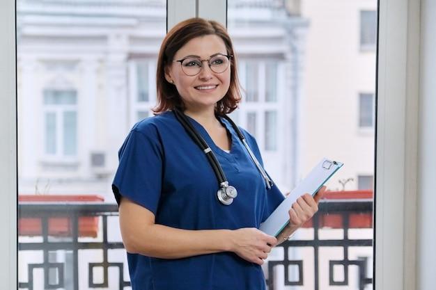 Portret van volwassen lachende arts met een stethoscoop klembord Premium Foto