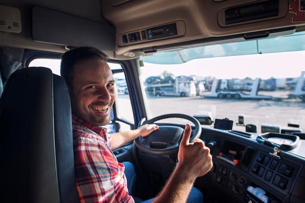 Portret van vrachtwagenchauffeur zitten in zijn vrachtwagen met duimen omhoog Gratis Foto