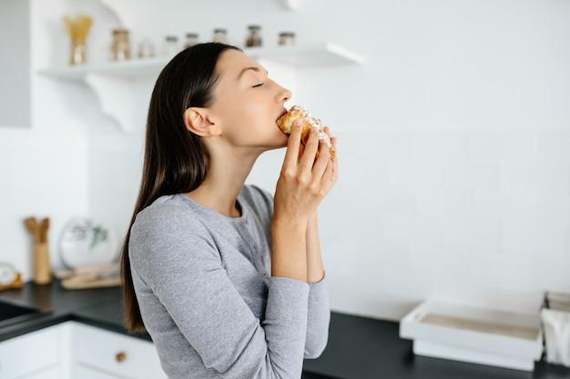 Portret van vreugde vrouw eet lekkere croissant thuis. ongezonde voeding concept. Gratis Foto