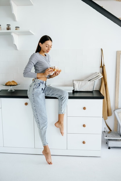 Portret van vreugde vrouw eet lekkere croissant thuis. Gratis Foto