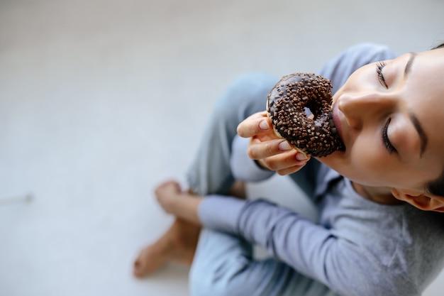 Portret van vreugde vrouw eet smakelijke donut thuis. Gratis Foto