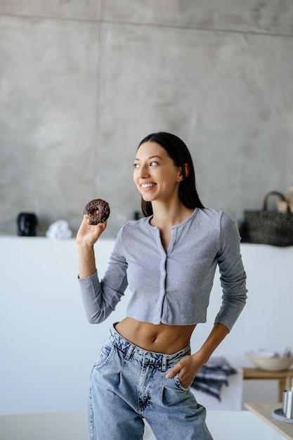Portret van vreugde vrouw met smakelijke donut thuis Gratis Foto