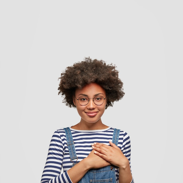 Portret van vriendelijk gestemde afro-amerikaanse vrouw in modieuze overall, houdt de handen op de borst, toont haar vriendelijkheid en sympathie, heeft vrolijke uitdrukking tevredengesteld, geïsoleerd over witte muur Gratis Foto