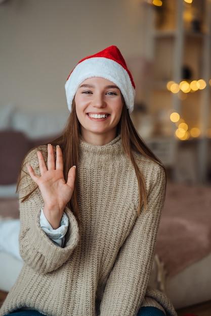 Portret van vriendelijke vriendelijke brunette vrouw in kerstmuts opgeheven hand zwaaien en hallo zeggen tegen camera, genieten van kersttijd. Gratis Foto
