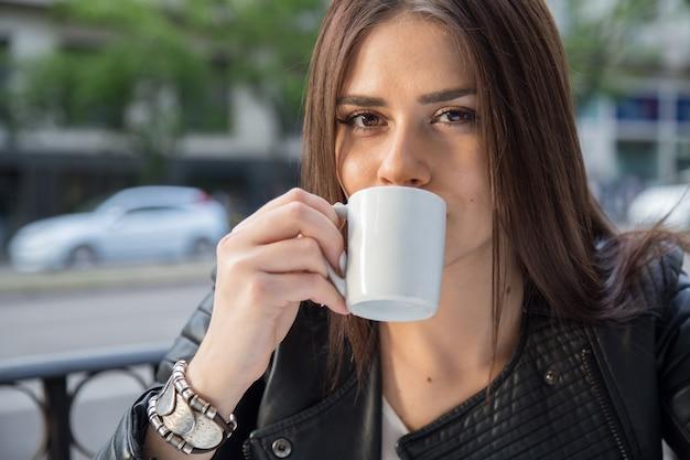 Portret van vrij kaukasische vrouw het drinken koffie op een terras in de straat. Premium Foto