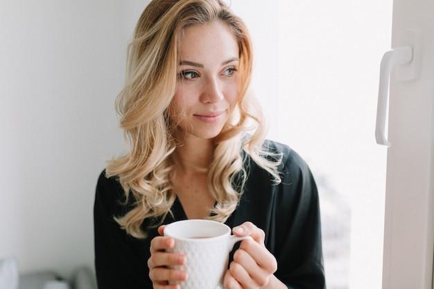 Portret van vrij mooi meisje met een kopje thee in de ochtend thuis close-up. ze zit op het raam en kijkt dromerig weg Gratis Foto