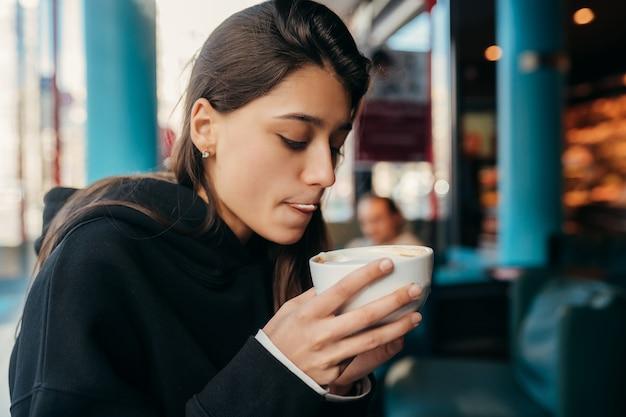 Portret van vrij vrouwelijke koffie drinken close-up. dame die een witte mok met hand houdt. Gratis Foto