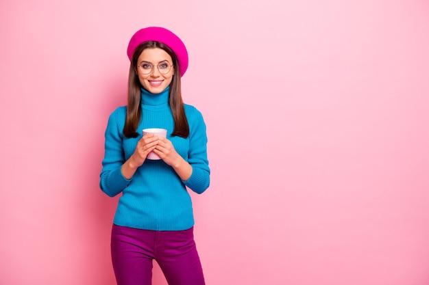 Portret van vrolijk dromerig meisje rust ontspannen ontbijt houden mok hete drank latte draag goed uitziende outfit. Premium Foto