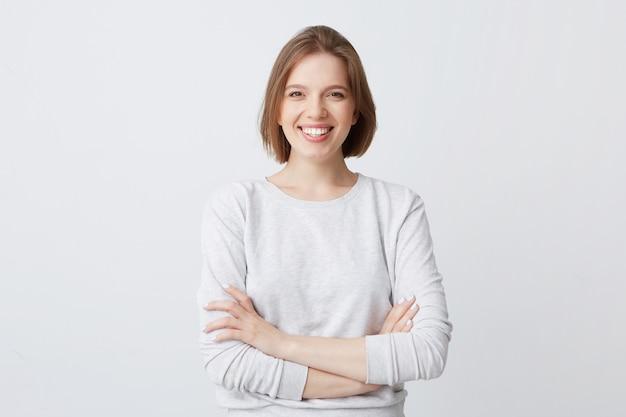 Portret van vrolijke aantrekkelijke jonge vrouw in longsleeve status met gekruiste en glimlachende armen Gratis Foto