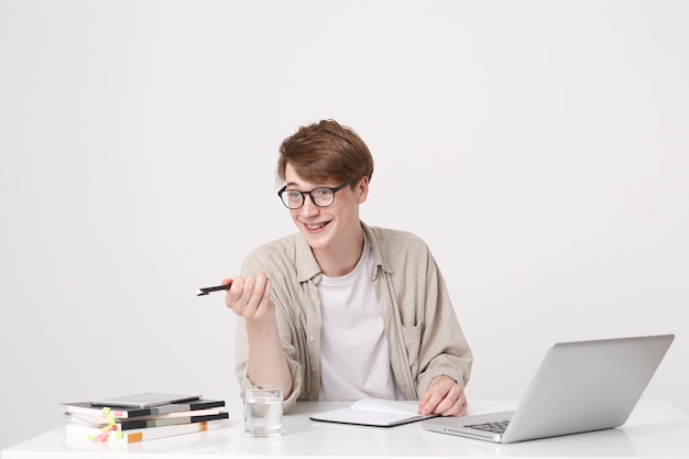 Portret van vrolijke aantrekkelijke jongeman student draagt een bril en een beige overhemd wijst naar de zijkant en studeert aan de tafel met laptop en notebooks geïsoleerd over witte muur Gratis Foto