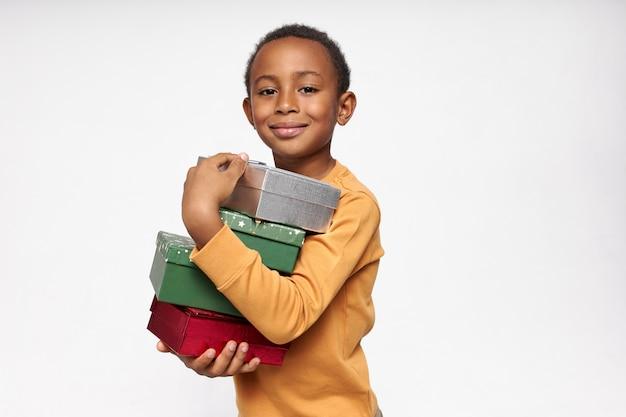 Portret van vrolijke afrikaanse jongen met dozen, cadeautjes ontvangen, kijkend naar de voorkant met een vrolijke, gelukkige glimlach Gratis Foto