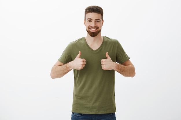 Portret van vrolijke en ondersteunende charmante bebaarde man in t-shirt duimen opdagen en glimlachen Gratis Foto