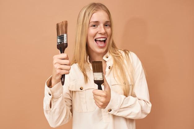 Portret van vrolijke gelukkige jonge blonde vrouw met tandenbeugels die verfborstels houden en opgewonden glimlachen, binnenmuren schilderen om het uiterlijk van haar slaapkamer te verbeteren Gratis Foto