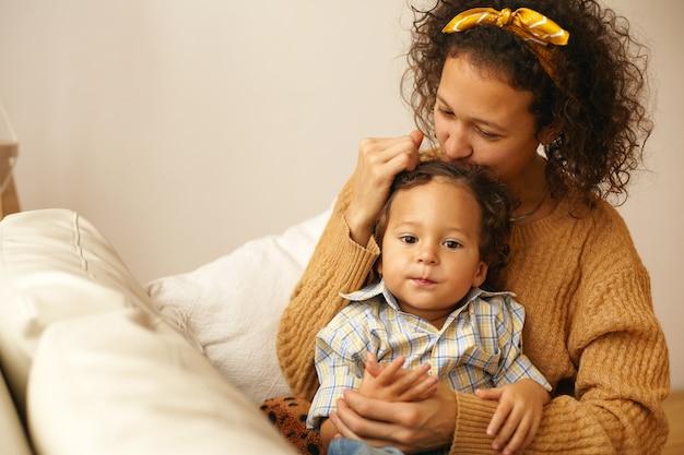 Portret van vrolijke jonge moeder in vrijetijdskleding uiting geven aan al haar liefde en tederheid aan drie-jarige zoontje, hem zachtjes kussen op het voorhoofd, moederschap verlof besteden aan de zorg voor peuter kind Gratis Foto