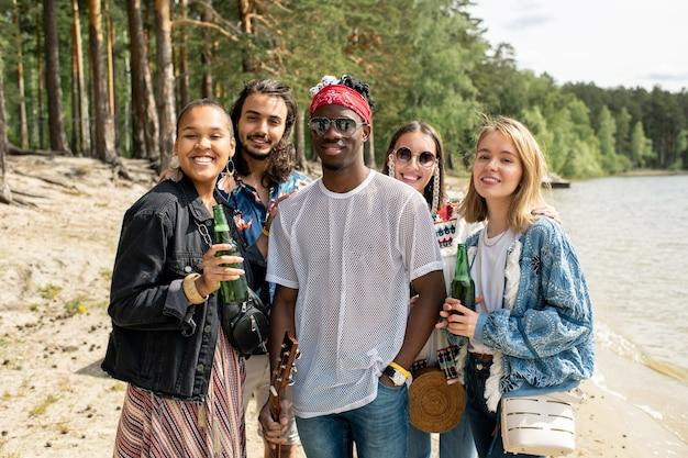 Portret van vrolijke jonge sex tussen verschillendre rassen vrienden die zich met bierflesjes op strand bevinden Premium Foto
