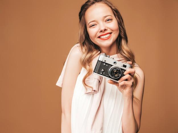 Portret van vrolijke jonge vrouw die foto met inspiratie nemen en witte kleding dragen. meisje dat retro camera houdt. model poseren Gratis Foto