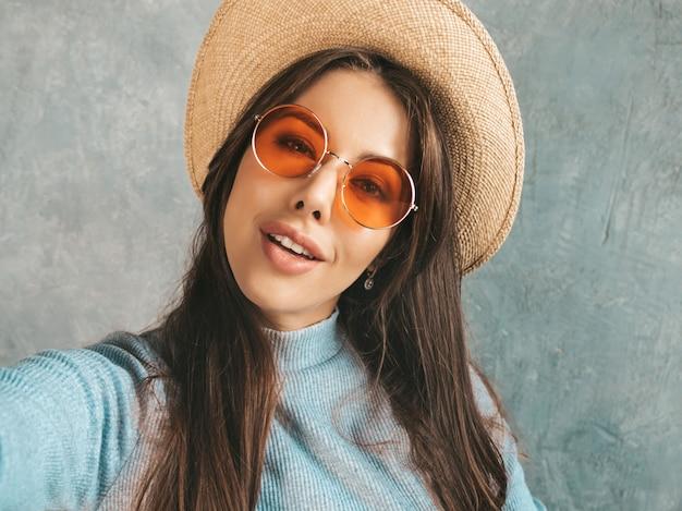 Portret van vrolijke jonge vrouw die foto selfie met inspiratie nemen en moderne kleren en hoed dragen. Gratis Foto