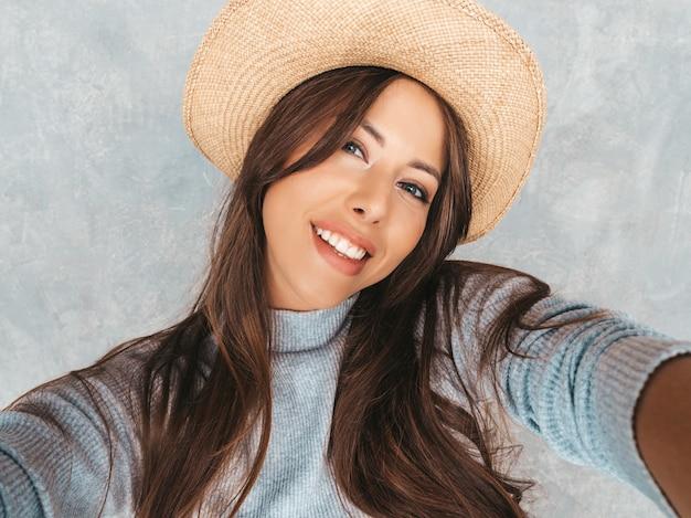 Portret van vrolijke jonge vrouw die foto selfie nemen en moderne kleren en hoed dragen. Gratis Foto