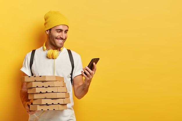 Portret van vrolijke mannelijke koerier controleert route naar huis van de klant op mobiele telefoon, houdt kartonnen dozen met pizza, terloops gekleed, luistert naar audio via koptelefoon Gratis Foto