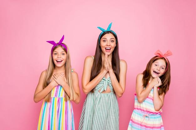 Portret van vrolijke mensen met hoofdbanden die wow omg gillen horen nieuws die kleurrijke kledingsrok dragen die over roze achtergrond wordt geïsoleerd Premium Foto