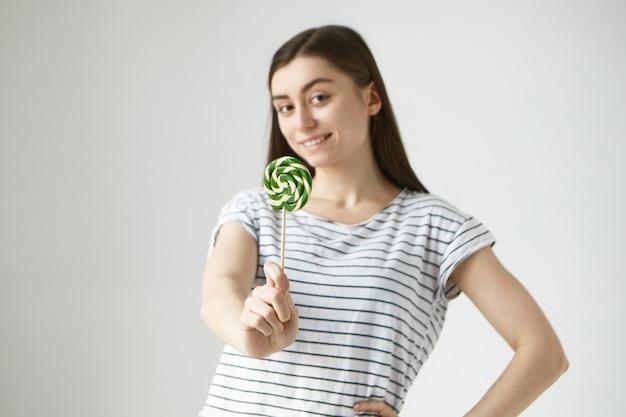 Portret van vrolijke mooie brunette jonge vrouw in gestreepte casual t-shirt met lolly, glimlachend met positieve vrolijke gezichtsuitdrukking. selectieve aandacht voor hard snoep Gratis Foto