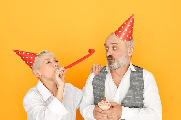 Portret van vrolijke rijpe vrouw blaast papier buis terwijl plezier op verjaardagsfeestje staande naast haar bejaarde bebaarde man in kegel hoed Gratis Foto