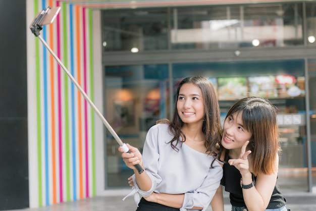 Portret van vrolijke twee glimlachende vriendinnen die een selfie maken bij winkelcomplex. Premium Foto
